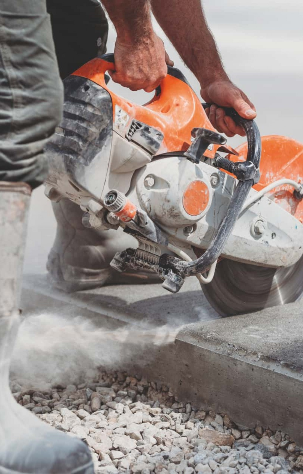 Ein Bauarbeiter benutzt eine Flex um Betonplatten zurecht zu schneiden